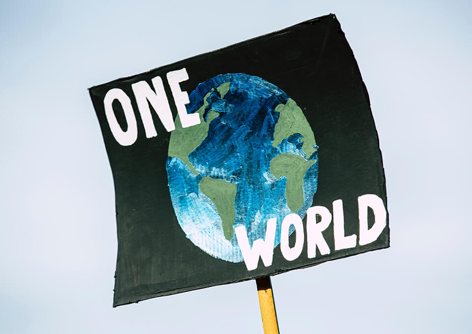 """A protest card showing Earth and a caption saying """"One World"""""""