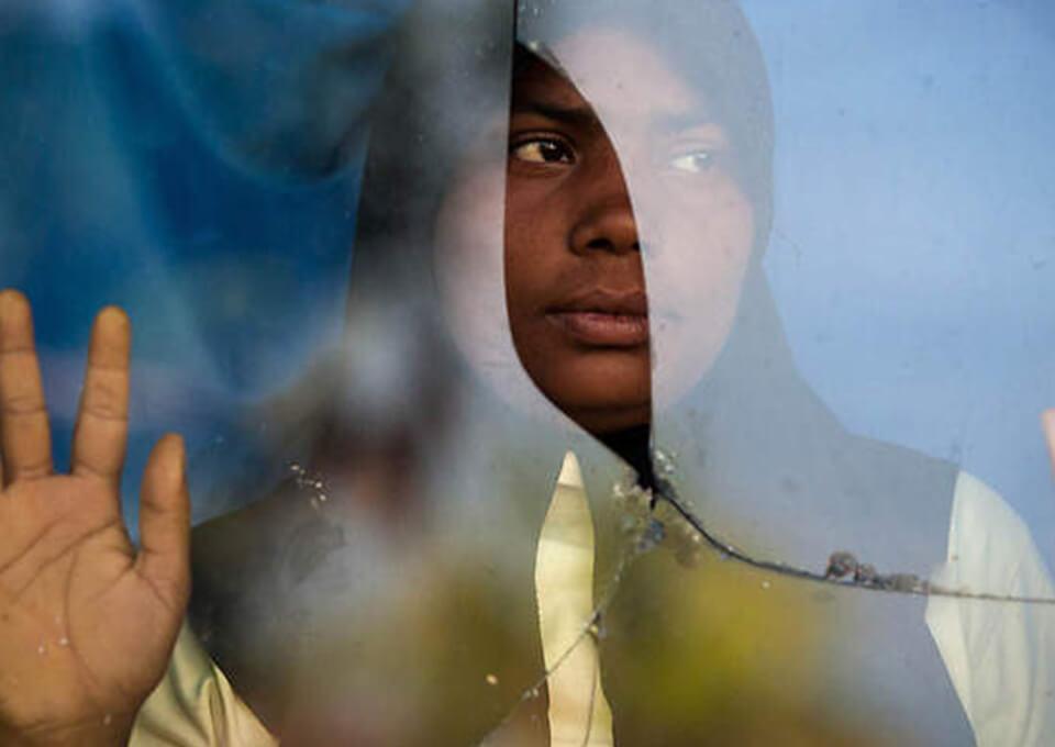 A woman staring through a broken glass.
